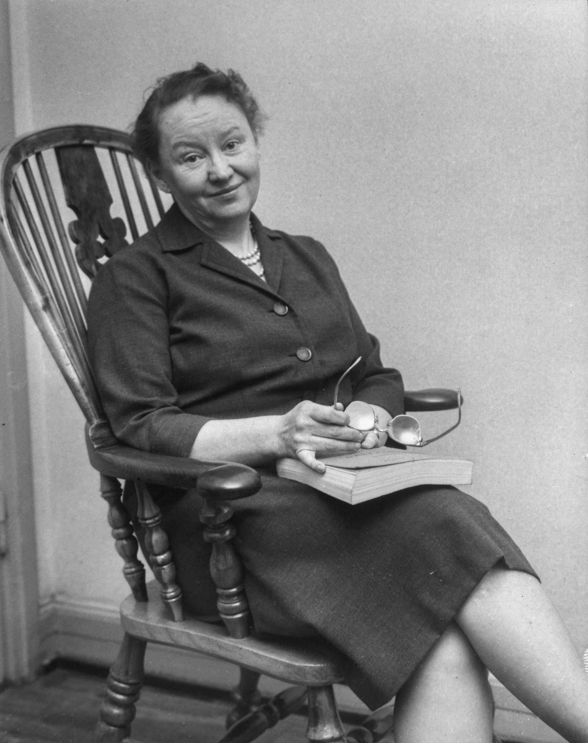 Stina Peyron sitter i en stol med en bok och ett par glasögon i handen.