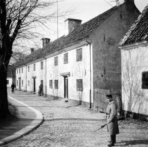 En vakt med gevär står utomhus på en gata i Landskrona citadell.